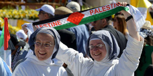 (RNS1-may11) A nun holds up a scarf that reads 'PALESTINE' before Pope Francis celebrates Mass in Manger Square outside the Church of the Nativity in Bethlehem, West Bank, on May 25, 2014. For use with RNS-PALESTINE-SAINTS, transmitted on May 11, 2015, Photo by Debbie Hill, courtesy of Catholic News Service.